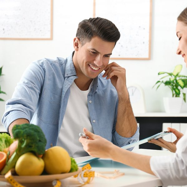 Young nutritionist consulting patient at table in clinic