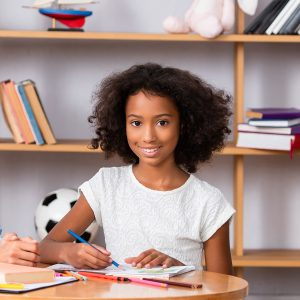 Happy psychologist and african american girl looking at camera near coffee table with colored pencils in office, banner